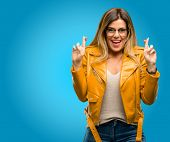 Beautiful young woman with crossed fingers asking for good luck, blue background poster