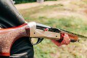 Man Hunter Holds A Shotgun With An Open Bolt And A Cartridge Inside The Trunk poster