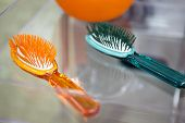 Two Hairbrushes Of Different Colors On A Clear Glass Table In The Bathroom poster