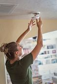 Changing the battery on a smoke alarm in an interior of a home. Woman standing on a step ladder and  poster