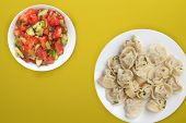 Dumplings On A White Plate On A Yellow Background. Top View Of Dumplings With Vegetable Salad. Asian poster