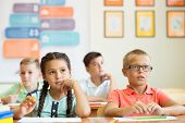 Clever Schoolchildren Studing And In Classroom At School poster