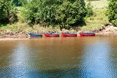 Blue Rowing Boat Followed By Three Red Rowing Boats, All Moored At The Side Of A River poster