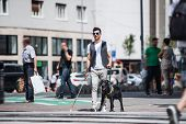 Young Blind Man With White Cane And Guide Dog Walking On Pavement In City. poster