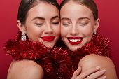 Image of a happy pretty young positive two women with bright red lipstick isolated over red wall bac poster
