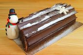Chocolate Yule Log Cake For With A Cute Snowman Marzipan For Christmas Celebration poster