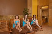 three smiling women sitting on loungers in front of sauna