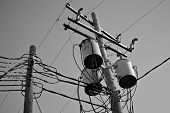 foto of utility pole  - Crowded utility poles with lots of wires in black and white - JPG