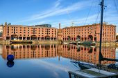 A Corner Of The Albert Dock In Liverpool. The Buildings And Moored Boats Are Beautifully Reflected I poster