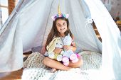 Adorable toddler sitting on the floor inside tipi around lots of toys at kindergarten poster