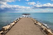 A Pier Of Stones, A Pier Going Into The Sea. Dramatic Sky With Dark, Heavy Clouds. poster