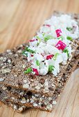 Fresh cheese salad with radish and herbs on crispbread