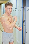 Bodybuilder opens locker and demonstrates tensed biceps in locker room after finishing training