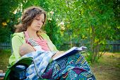 stock photo of breastfeeding  - mother breastfeeding her baby seating on a chair outside and reading the book - JPG