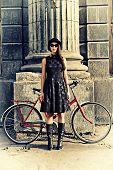 pic of bowler  - Beautiful brunette standing near her old bicycle over city background - JPG