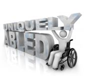 stock photo of disabled person  - A person in a wheelchair beside the words Uniquely Abled - JPG