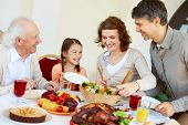 stock photo of christmas meal  - Portrait of happy family sitting at festive table while having Thanksgiving dinner - JPG