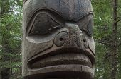 foto of totem pole  - Closeup of face on wooden cedar Tlingit totem pole in pine forest in Sitka Alaska - JPG