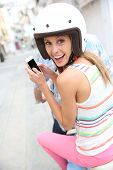 Cheerful girl riding motorcycle and using smartphone