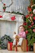 Little girl sits on cardboard gift box with contented look under Christmas tree, holding gingerbread