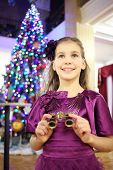 Girl with binocular stands near christmas tree in big theater
