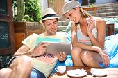 Young couple on holidays connected to internet with tablet