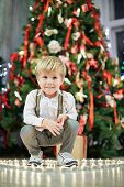 Little boy sits squatted among burning tealights that stand on floor in shape of heart under Christm