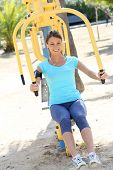 Fitness girl exercising with outdoors weight machines
