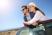 Couple enjoying view from top of convertible car