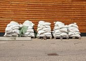 picture of sandbag  - Sandbags in five piles with wooden wall in background
