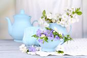 Beautiful spring flowers in cups on wooden table