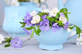Beautiful spring flowers in cup on wooden table