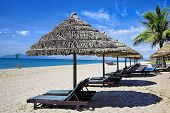 Tropical beach with straw umbrella and chairs