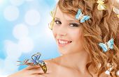 health and beauty concept - happy teenage girl with butterflies in hair and one sitting on her hand