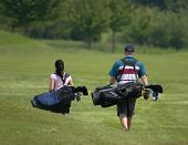 image of golf bag  - couple walking down fairway