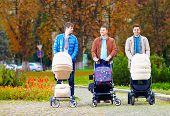 stock photo of buggy  - fathers walking with buggies in city park parental leave - JPG
