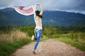 picture of dirt road  - Happy young caucasian woman outdoor on a rural dirt road in the countryside dancing - JPG