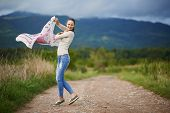 foto of dirt road  - Happy young caucasian woman outdoor on a rural dirt road in the countryside dancing - JPG