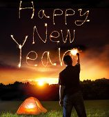 image of halo  - young man drawing happy new year words by sparkling stick - JPG