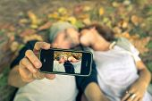 picture of two women taking cell phone  - couple kissing while taking a selfie with smart phone - JPG