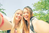 stock photo of two women taking cell phone  - Two pretty young women taking selfie with phone - JPG