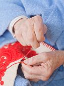 stock photo of welts  - Old woman sitting on the bed and sewing - JPG