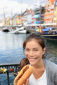 Woman eating traditional danish fast food snack hot dog. Girl enjoying hot dogs outside in Nyhavn waterfront canal street of Copenhagen, Denmark. poster