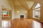 stock photo of ivory  - Spacious living room with high ceiling big arch window fireplace and new hardwood floor in empty new house - JPG