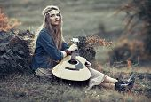 stock photo of hippy  - Beautiful hippie girl with guitar sitting on field near stone