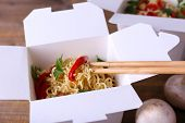 foto of chinese parsley  - Chinese noodles in takeaway boxes with mushrooms and parsley on wooden background - JPG