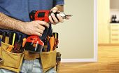 stock photo of hand drill  - detail on handyman manual worker tools belt and red drill in his hands - JPG