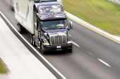 stock photo of tractor-trailer  - Tractor trailer on a two lane road with motion blur effect - JPG