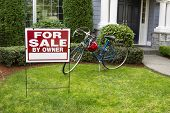 stock photo of yard sale  - Closeup view of Modern Suburban Home with for Sale Real Estate Sign in front yard and bicycle and house in background - JPG