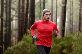 stock photo of long distance  - Running man in forest woods training and exercising for trail run marathon endurance race - JPG